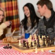 Playing chess winter chalet friends laughing — Stock Photo