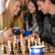 Young people play chess winter cottage countryside — Stock Photo