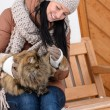 Young woman sitting bench winter stroking cat — Stock Photo