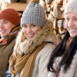 Stock Photo: Three young people winter fashion wooden logs