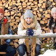 Stock Photo: Young people sitting outside winter clothes wood