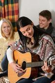 Молодые друзья в коттедже зимой играть на гитаре — Стоковое фото