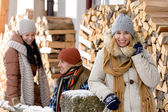 Young people outside winter cottage wooden logs — Stock Photo