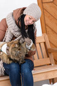 Young woman sitting bench winter stroking cat — Stockfoto