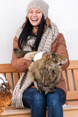 Young woman stroking cat sitting winter bench — Stockfoto