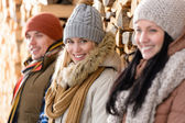 Three young people winter fashion wooden logs — Stock Photo