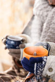 Steaming cups of tea winter hands holding — Stock Photo