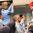 Air stewardess check ticket airplane cabin smiling — Stock Photo