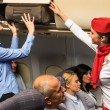 Flight attendant help passenger with luggage cabin — Stockfoto