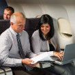 Businesspeople working on computer flight airplane — Stock Photo