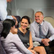 Business people passengers flying airplane talking — Stock Photo