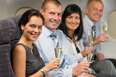 Business people flying airplane drink champagne — Stock fotografie