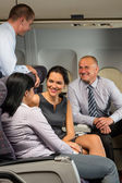 Business people passengers flying airplane talking — Stock fotografie