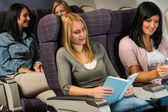 Young woman passenger read book airplane flight — Foto Stock