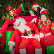 Tired Santa Clause with elf helper sleep chair — Stockfoto