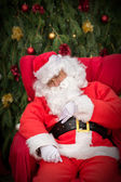 Sleeping Santa Clause on red Christmas armchair — Stock Photo