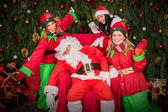 Tired Santa Clause with elf helper sleep chair — Stock Photo