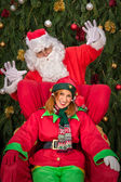 Santa Clause with elf helper Xmas armchair — Stock Photo