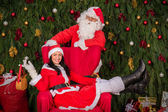 Santa Clause woman sitting on Christmas armchair — Stock Photo