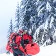 Ski patrol carry injured person in stretcher — Stock Photo