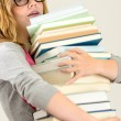 Worried student girl carry stack of books — Stock Photo
