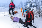 Rescue ski patrol help injured woman skier — Stock Photo