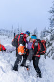 Ski patrol carry injured woman skier stretcher — Stock Photo