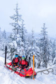 Ski patrol with rescue sled injured woman — Stock Photo