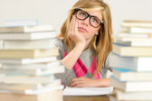 Bored student girl between stack of books — Stock Photo