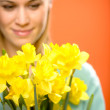 Stock Photo: Womwith spring yellow flower narcissus