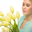 Woman looking down yellow tulip spring flowers — Stock Photo