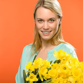 Spring woman hold yellow narcissus flowers — Stock Photo