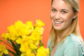 Smiling woman with spring yellow narcissus flowers — Stock Photo
