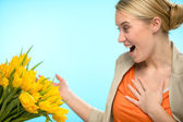 Surprised woman receive bouquet of yellow tulips — Stock Photo