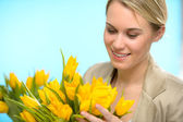 Woman looking down at spring yellow tulips — Stock Photo