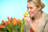 Woman smelling one yellow tulip spring flowers — Stock Photo