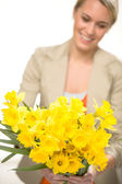Yellow spring narcissus woman in background — Stock Photo