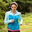 Running woman in forest fitness training — Stock Photo