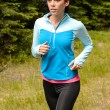 Stockfoto: Sportive womrunning  through meadow