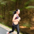 Young woman running outdoors motion blur — Stock Photo