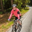 Stock Photo: Wommountain biking in sunny forest smiling