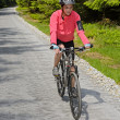 Stock Photo: Womriding bike on sunny cycling path