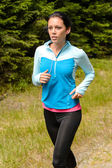 Sportive woman running  through meadow — Stock Photo