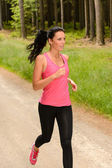 Sportive woman running through forest — Stock Photo