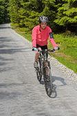 Woman riding bike on sunny cycling path — Foto de Stock