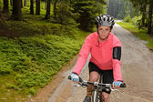 Woman mountain biking through forest road — Stock Photo