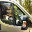 Stock Photo: Courier man driving car delivering postal package
