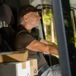 Stock Photo: Courier mdriving cargo car delivering package