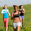 Three girls jogging downhill summer meadow — Foto Stock