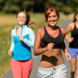 Three friends running outdoors smiling — Foto de Stock